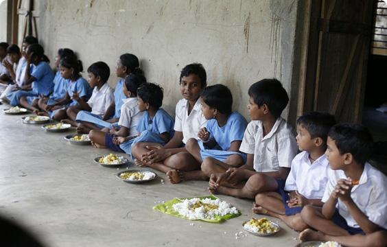 Row of children sitting on the floor eating